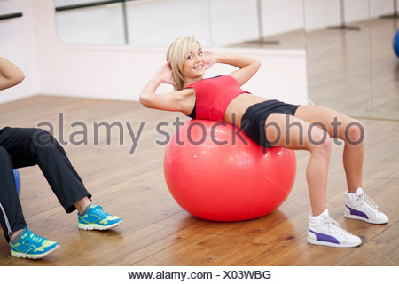 Young woman lying on exercise ball in aerobics class - Stock Photo