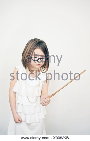 Frowning girl holding stick - Stock Photo