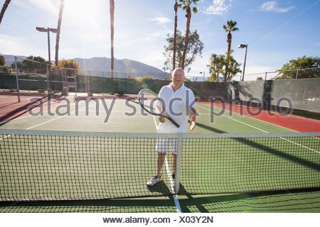 Portrait of senior tennis player offering handshake on court - Stock Photo