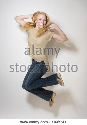 Portrait of mid-adult woman jumping - Stock Photo