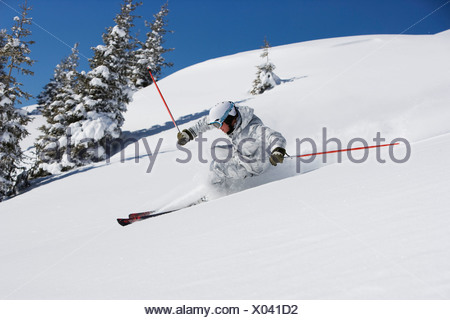 Man in white & grey camo suit carving. - Stock Photo
