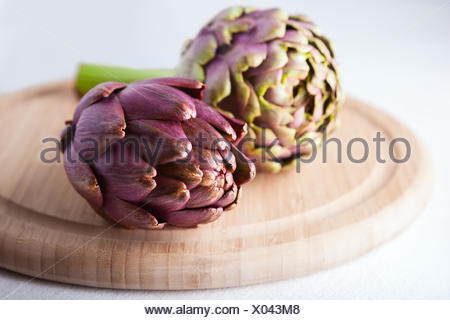 Two artichokes lying on a wooden plate - Stock Photo