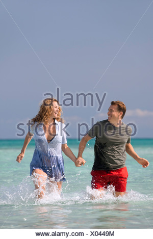 Couple walking in water, holding hands - Stock Photo