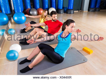 Pilates people group exercise man and women at fitness gym. - Stock Photo