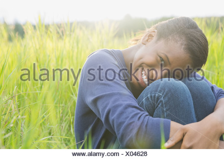 Portrait of happy girl sitting in a field - Stock Photo