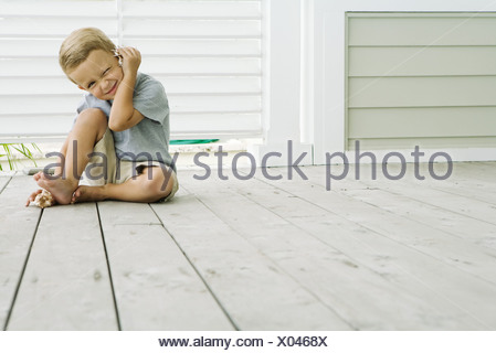 Boy sitting on the ground listening to seashell, squinting at camera, smiling - Stock Photo