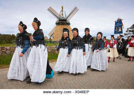Women in traditional frisian costumes, in front of a windmill, Nebel, Amrum island, North Sea, North Friesland, Schleswig-Holste - Stock Photo