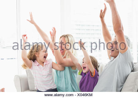 Family celebrating success while watching TV - Stock Photo