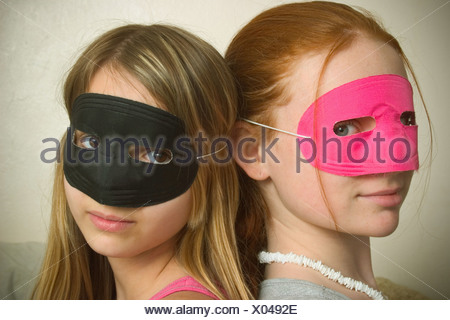 Long red hair and blond hair teen girls, both wearing masks over their eyes, posing together. - Stock Photo