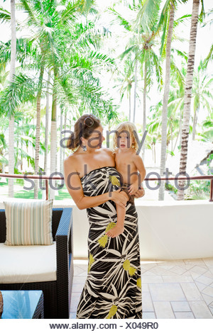 Stylish woman with baby near palm trees - Stock Photo