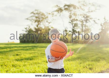 Portrait of cute boy holding basketball on field - Stock Photo