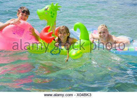 Children on floaties in lake - Stock Photo