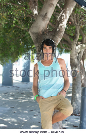 Portrait of smiling young man wearing headphones and leaning against tree in park - Stock Photo