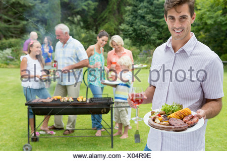 Portrait of smiling man holding plate of barbecue and glass of wine with family in background - Stock Photo