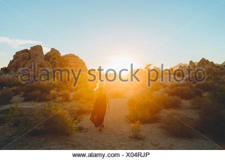 USA, California, Joshua Tree National Park, Woman wearing dress hiking at sunset