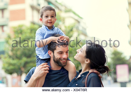 Father carrying son on shoulders with woman - Stock Photo