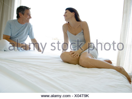 Mature couple sitting on bed, smiling at each other - Stock Photo