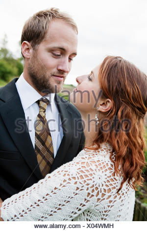 Sweden, Smaland, Bride and groom standing face to face - Stock Photo