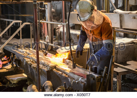 Worker testing molten metal at aluminum recycling plant - Stock Photo