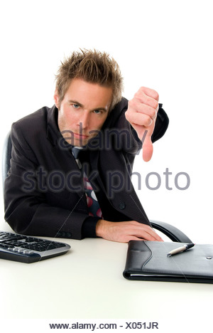 dissatisfied office clerk at his desk, making thumb down - Stock Photo