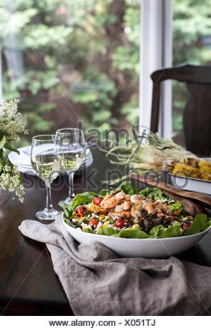 A big bowl of grilled shrimp and corn salad accompanied with two glasses of white wine are photographed from the front view. - Stock Photo