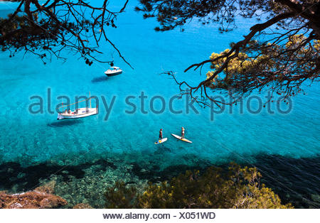 man and woman stand up paddle in turquoise waters - Stock Photo