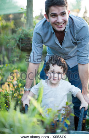 Portrait of mid adult man and son pushing wheelbarrow in allotment - Stock Photo