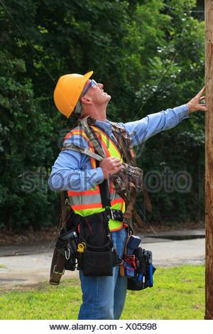 Communications engineer preparing to climb pole - Stock Photo