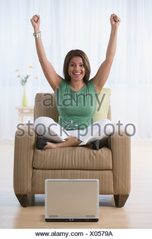 Indian woman cheering in armchair - Stock Photo