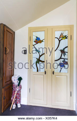 Entryway with ragdoll and wooden built-in armoire and closet doors with satined glass panels inside an old reconstructed 1886 Canadiana cottage style residential home, Quebec, Canada - Stock Photo