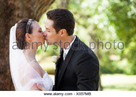 Romantic newlywed couple kissing in park - Stock Photo