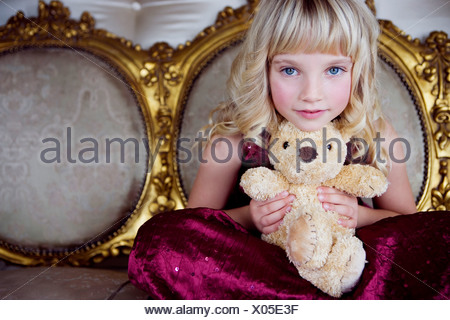 Portrait of a little girl holding a teddy bear - Stock Photo