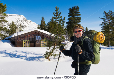 Happy woman with backpack and ski poles in front of mountain hut and trees against clear blue sky - Stock Photo