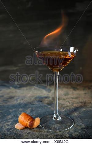 Flaming cocktail on dark stone bar with orange garnish. - Stock Photo