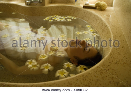 Young woman taking bath with flower petals - Stock Photo