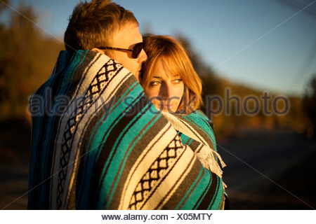 Couple wraps themselves in a blue and white blanket and watch the sunset. - Stock Photo