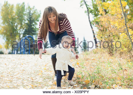 Mother helping baby girl to walk in park - Stock Photo