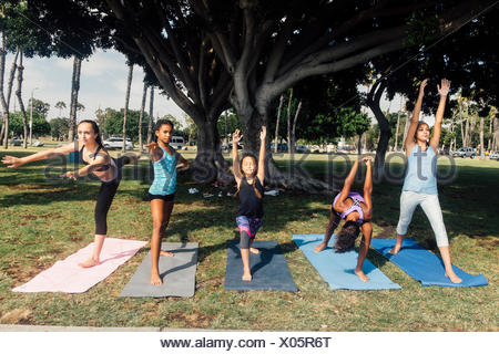 Girls and teenage schoolgirls practicing yoga warrior pose on school playing field - Stock Photo