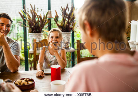 Happy girl having cookie while having breakfast with family at home - Stock Photo