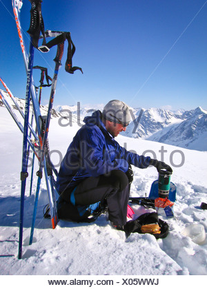 Skier resting and melting snow on a stove on Trail Glacier,  Kenai Mountains, Winter in Southcentral Alaska - Stock Photo