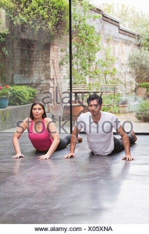 Couple practicing yoga together at home - Stock Photo