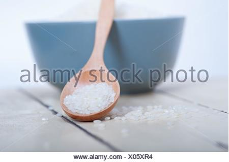 raw white rice on wood spoon and blue bowl extreme close up. - Stock Photo