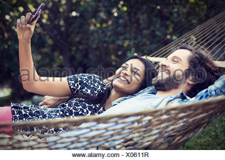 A couple, a young man and woman lying in a large hammock in the garden, taking a selfy of themselves. - Stock Photo