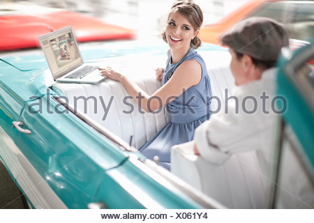 Man watching woman use laptop in back seat of convertible - Stock Photo