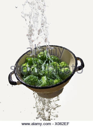 Water falling through colander with fresh broccoli - Stock Photo
