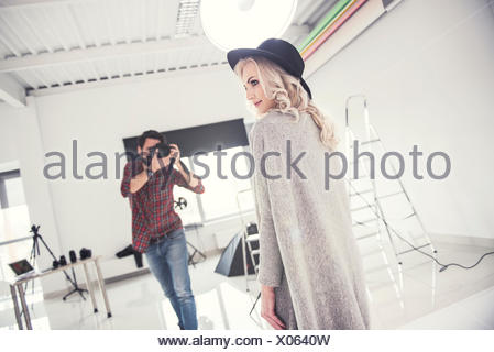 Male photographer photographing female model on studio white background - Stock Photo