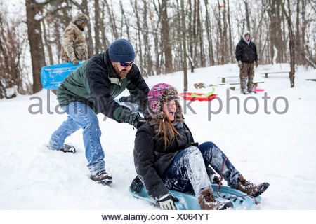 Mid adult couple and teenage son playing on toboggans - Stock Photo