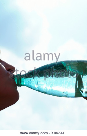 Woman drinking water from a bottle - Stock Photo