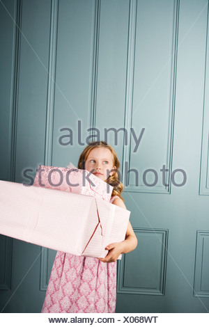 little girl carrying presents - Stock Photo