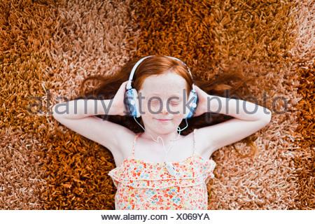 Girl listening to headphones on carpet - Stock Photo